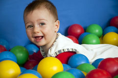 Baby with balls. Close up portrait of a baby boy playing with colorful plastic balls in an indoor playground Stock Photo