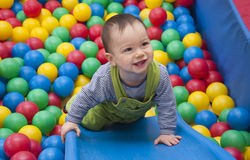 Baby in balls. Cute baby boy playing with colorful plasic balls in an indoor playground Royalty Free Stock Images