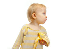 Baby with banana looking on side isolated on white Stock Photo