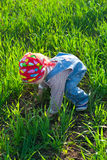 Baby in the bandana on all fours in the field Royalty Free Stock Images