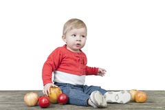 Baby with basket of apples, seated on a old wooden table Royalty Free Stock Photography