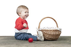 Baby with basket of apples, seated on a old wooden table Stock Photos