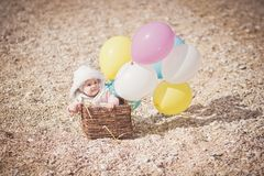 Baby in a basket with balloons. Baby girl sitting in a basket with balloons Royalty Free Stock Photography