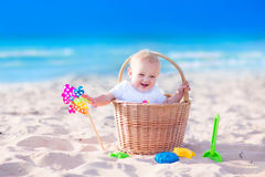 Baby in a basket on the beach. Happy funny baby, adorable blond laughing boy sitting in a basket playing with plastic beach toys, colorful bucket and shovel royalty free stock photography