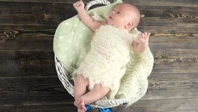 Baby in basket with bow. Small child on wooden background stock video