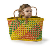 Baby in Basket. Baby girl sits and hides inside a shopping basket Royalty Free Stock Photo