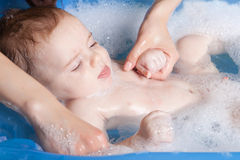 Baby in bath. Beautiful young baby taking a bath with foam stock image