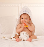 Baby after the bath. Baby with a towel after the bath biting a yellow toy stock image