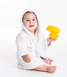Baby after bath. Baby in a bathrobe after a bath with yellow toy royalty free stock image