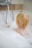 Baby in bath foam. Rear view Stock Images