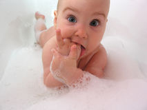Baby in bath. hand in mouth Stock Photography