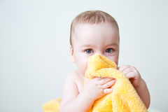 Baby After Bath Hiding Behind Yellow Towel. Caucasian baby boy hiding face behind soft fluffy yellow towel; wiping or drying face; hiding a secret Stock Images