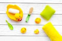 Baby bath set with yellow rubber duck. Soap, sponge, brushes, towel on white wooden background top view Stock Image