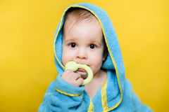 Baby after a bath sits and chews toy Royalty Free Stock Images