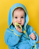 Baby after a bath sits and chews toy Royalty Free Stock Photos