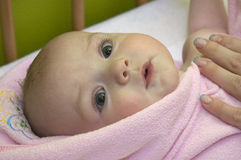 Baby after bath in towel. Baby lying on back being dried by its mother after bath Stock Image