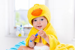 Baby in bath towel with tooth brush. Little baby in yellow duck towel brushing teeth on changing table after bath. Infant boy with tooth brush. Dental hygiene Stock Photography