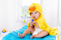 Baby in bath towel with tooth brush. Little baby in yellow duck towel brushing teeth on changing table after bath. Infant boy with tooth brush. Dental hygiene Stock Photo