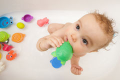 Baby in bath tub with toys Stock Photos