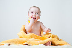 Baby After Bath Wrapped in Yellow Towel Sittin. Baby boy after bath wrapped in a yellow fluffy and soft towel with a small yellow ball in his right hand and Stock Image