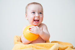 Baby After Bath Wrapped in Yellow Towel Sitting. Baby boy after bath wrapped in yellow towel sitting with yellow circular textured toy and smiling showing bottom Stock Image