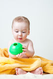 Baby After Bath Wrapped in Yellow Towel Sitting. Baby boy after bath wrapped in soft and fluffy yellow towel sitting holding and looking at a green circular toy Royalty Free Stock Image