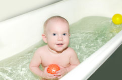 Baby is bathed in light bathroom Royalty Free Stock Photos