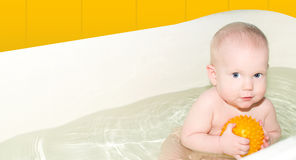 Baby is bathed in light bathroom Stock Image