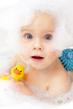 Baby bathing. Cute little baby girl bathing in soapsuds stock images