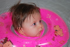 Baby bathing. The little girl bathes in a special circle of water stock image