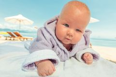 Baby in bathrobe. Cute baby wearing bathrobe on the sunbed Royalty Free Stock Images