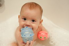 Baby in the bathroom playing with two toys. Selective focus on baby head stock photos