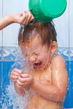 Baby in bathroom pouring water Royalty Free Stock Image