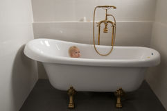 Baby in a bathtub 01. Baby sitting an a bathtub with golden tap Stock Image