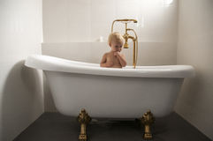 Baby in a bathtub 02. Baby sitting an a bathtub with golden tap Stock Photography