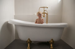 Baby in a bathtub 03. Baby sitting an a bathtub with golden tap Stock Photo