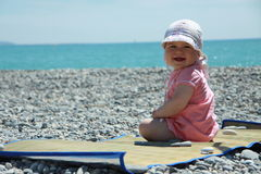 Baby on the beach. Baby girl (1 year old) sitting on the rocky beach of French Riviera and smiling Stock Photography