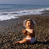 Baby at the beach. Young baby with sun hat at the beach Royalty Free Stock Photo