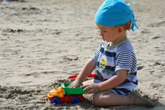 Baby on beach. Sit and play Stock Image