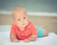 Baby on the beach. Cute baby laying on the sunbed at the beach Royalty Free Stock Photography