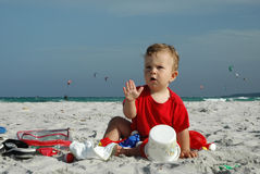 Baby on the beach. A little caucasian   baby boy in the face sitting in the sand and playing with her toys on the beach on a windy summer day Royalty Free Stock Photography