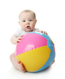 Baby with beach ball. Adorable baby playing with a colorful beach ball, isolated on white Royalty Free Stock Photos