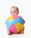 Baby with beach ball. Adorable baby playing with a colorful beach ball, isolated on white Royalty Free Stock Images