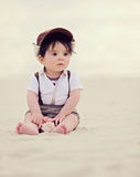 Baby on the beach. Beautiful beach scene with baby boy holding a sea shell Stock Image