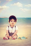 Baby on the beach. Beautiful beach scene with sea shells and rainbow in the background Stock Image