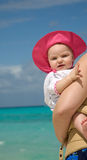 Baby on beach being held. By mother with blue water in background Stock Photography