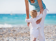Baby on beach climbing mothers hands Royalty Free Stock Photo