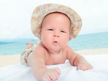 Baby on the beach. Cure baby laying on the sunbed at the beach Stock Images