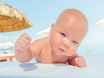 Baby on the beach. Cure baby laying on the sunbed at the beach Stock Photography