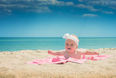Baby on a beach. Cure baby laying on the sunbed at the beach of Black sea Stock Image